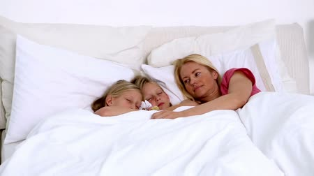 quarto doméstico : Mother sleeping peacefully with her twin girls at home in the bedroom