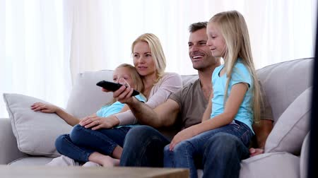 assistindo : Members of a family watching television on sofa and smiling Vídeos