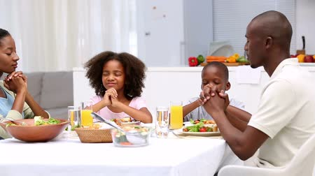 guy home : Family saying grace before eating their dinner at home