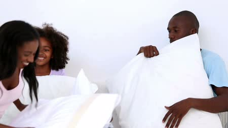 almofada : Family playing together with pillows at home on bed