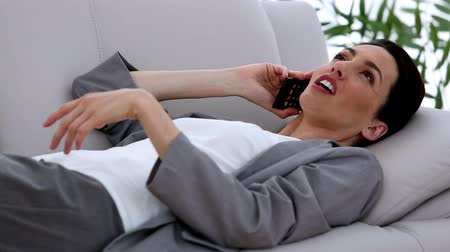 resting : Attractive businesswoman relaxing on the couch while she is on the phone
