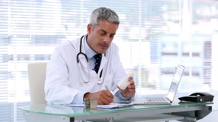 наркотик : Doctor looking at pills while writing a prescription in his office