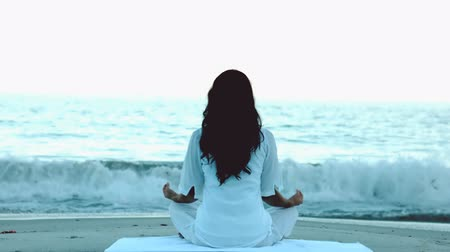meditação : Woman practicing yoga in front of the sea in slow motion