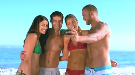 Картинки : Group of friends taking self pictures on the beach in slow motion