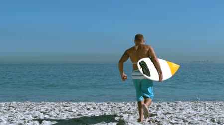 szörfös : Handsome man with a surfboard running into the sea in slow motion Stock mozgókép