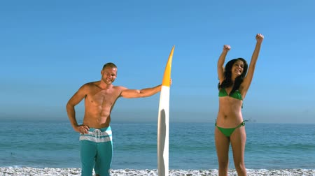 surf : Attractive girl jumping next to a friend with a surfboard in slow motion Dostupné videozáznamy