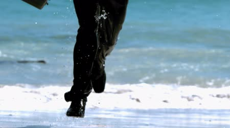 corrida : Businessman running out the sea in slow motion Vídeos