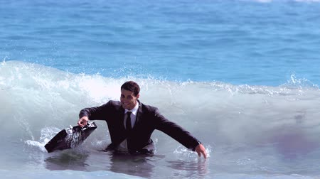 biznesmen : Businessman jumping in the waves in slow motion
