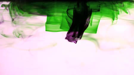 inkoust : Pink and green ink swirling in water on white background in slow motion
