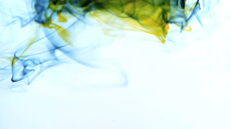 yellow ink : Yellow and blue ink swirling in water on white background in slow motion Stock Footage