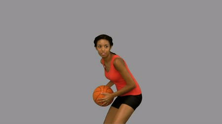 top sürme : Woman catching and throwing a basketball on grey screen in slow motion