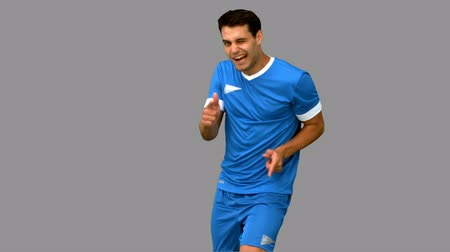 ruch : Happy football player celebrating a goal on grey screen in slow motion Wideo