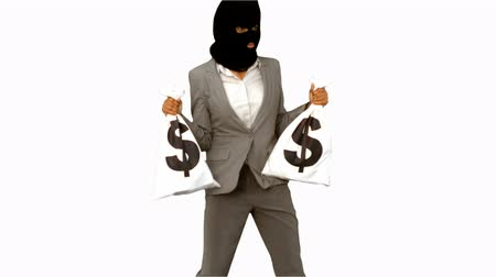 ladrão : Burglar wearing balaclava and holding money bags on white screen in slow motion