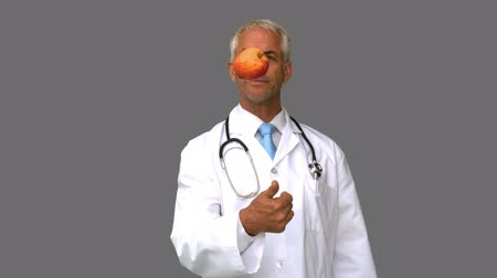 doktor : Doctor throwing an apple on grey screen in slow motion Stok Video