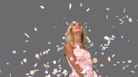 tenso : Pretty woman in ballgown admiring petals falling on grey screen in slow motion