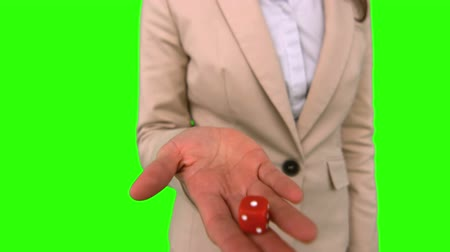 dobókocka : Businesswoman throwing a die on green screen in slow motion Stock mozgókép
