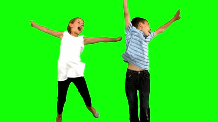 rodzeństwo : Siblings jumping together on green screen in slow motion