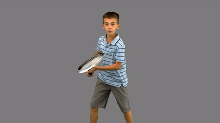 kaukázusi : Little boy playing tennis on grey screen in slow motion Stock mozgókép