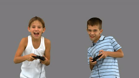 kaybediyor : Siblings playing video games on grey screen in slow motion Stok Video