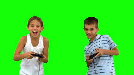 соперничество : Siblings playing video games on green screen in slow motion