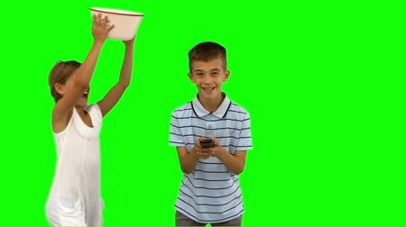 pipoca : Sister pouring popcorn on brothers head on green screen in slow motion