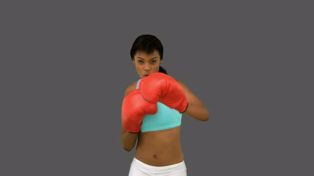 boxe : Gorgeous woman with red gloves boxing on grey background