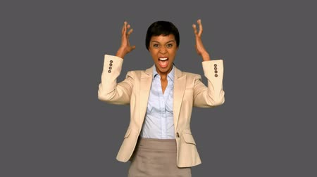 tenso : Irritated businesswoman gesturing on grey background