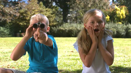 потрясенный : Brother with binoculars showing something to his sister in slow motion