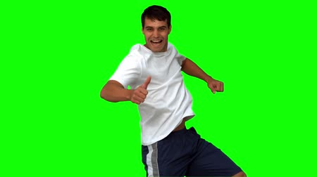 tenso : Handsome man giving thumbs up on green screen in slow motion