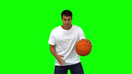 top sürme : Man dribbling with a basketball on green screen in slow motion
