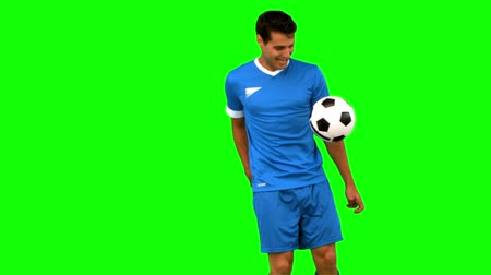 jogador : Handsome man juggling a football on green screen in slow motion