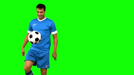 caucasiano : Man playing with a football on green screen in slow motion