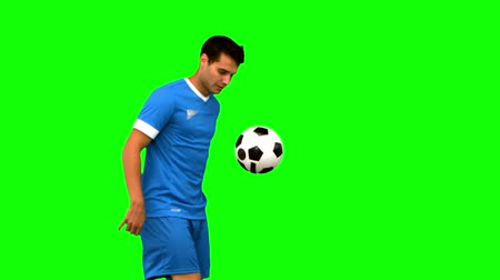 top sürme : Handsome man playing with a football on green screen in slow motion