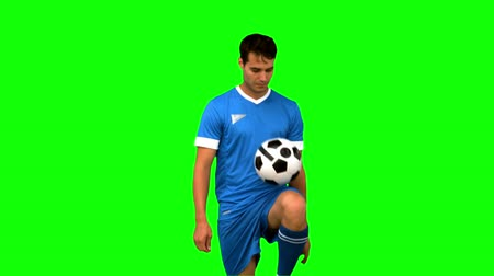 jogador : Man juggling a football with his knee on green screen in slow motion