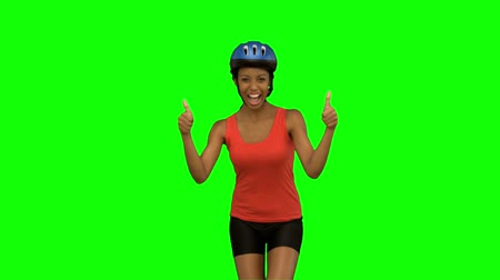 tenso : Cyclist woman giving thumbs up on green screen in slow motion