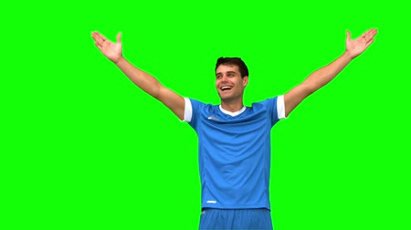jogador : Football player waving a kissing at people on green screen in slow motion
