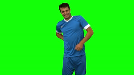 zpátky : Football player suffering from back pain on green screen in slow motion