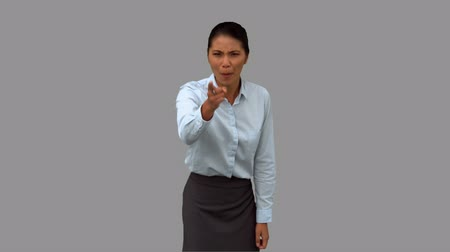 gritar : Angry businesswoman pointing on grey screen in slow motion