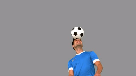 top sürme : Man juggling a football with his head on grey screen in slow motion