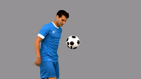 top sürme : Handsome man playing with a football on grey screen in slow motion