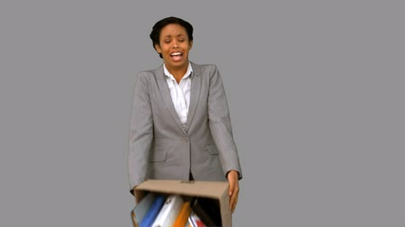 desistir : Fired businesswoman dropping a box on grey screen in slow motion
