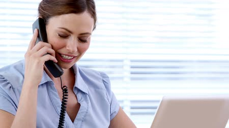 диалог : Smiling businesswoman talking on the phone in her office