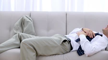 lefekvés : Businessman crashing down onto sofa after long days work
