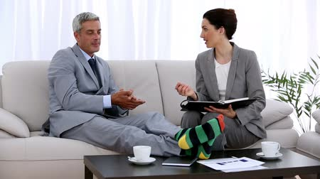 resting : Businessman in socks making an appointment with a colleague while they are sat on a couch Stock Footage