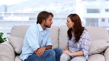 psikoloji : Couple discussing in therapy sitting on a sofa