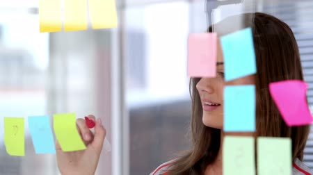 kreatywne : Woman writing on sticky note in creative office Wideo