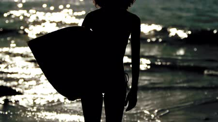 серфер : Silhouette of an attractive woman holding her surfboard in slow motion