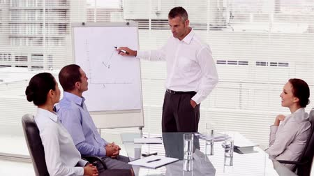 conferência : Smiling businessman pointing at a growing chart during a meeting