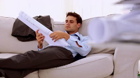 krawat : Businessman lying on couch and looking at a document in waiting room Wideo