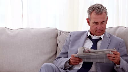suit and tie : Smiling businessman reading newspapers in a waiting room  Stock Footage
